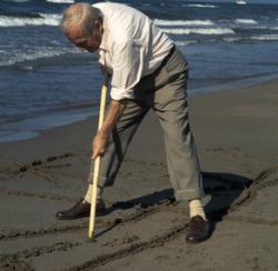 """Exposició """"Joan Miró. Apunts de taller"""". Foto de Ralph Hermann on Miró dibuixant a la sorra de la platja (1970). Font: web de la Casa de Cultura de la Diputació de Girona"""